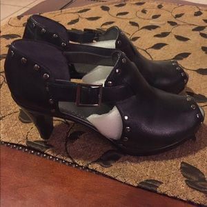 Leather black heeled shoes with silver studs.